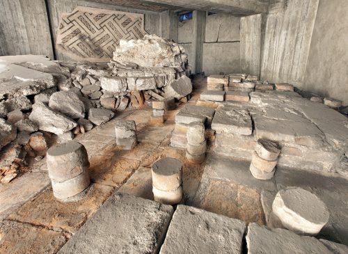 Resti del tepidarium conservati in un sotterraneo in corso Europa. In primo piano si riconoscono i pilastrini in mattoni cilindrici che sorreggevano il pavimento e permettevano la circolazione di aria calda sotto di esso, così da riscaldarlo.