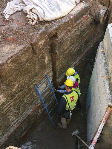 Gli archeologi fanno un'attenta analisi del lato meridionale della muratura messa in luce in piazza Resistenza Partigiana nel cantiere per la Stazione De Amicis della linea M4.